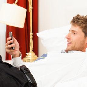 Un uomo d'affari usa lo smartphone nel suo letto d'hotel