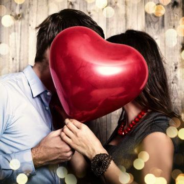 foto de una pareja detrás de un globo de corazón