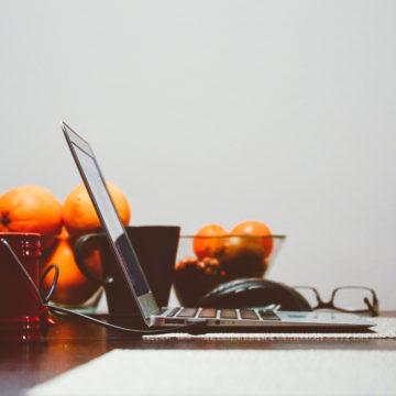 Un computer ed un cesto di arance