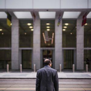 Hombre en traje gris delante de un edificio