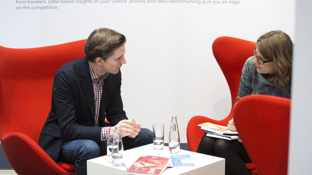 trivago MD Johannes Thomas speaks with a journalist at ITB Berlin