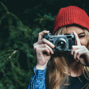 a woman with a red beanie and an old 35mm camera