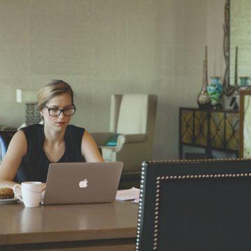 Chica trabajando en un cafeteria con un ordenador Mac