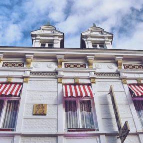 πρόσοψη ξενοδοχείου με κόκκινες και λευκές τέντες