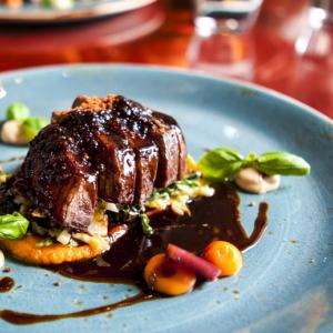 Hotel Gourmet: un gustoso taglio di bistecca servito con una colorata guarnizione.