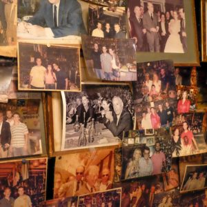 the wall at taverna tripa is covered with photos throughout the decades