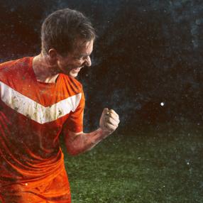 Futbolista con uniforme rojo celebrando la victoria