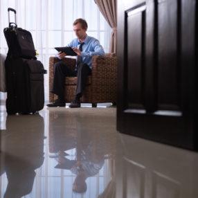 Ein Hotelier heißt einen Gast an der Rezeption willkommen
