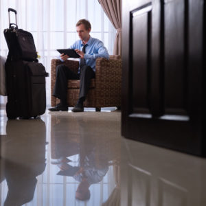 A man uses a tablet to book a hotel