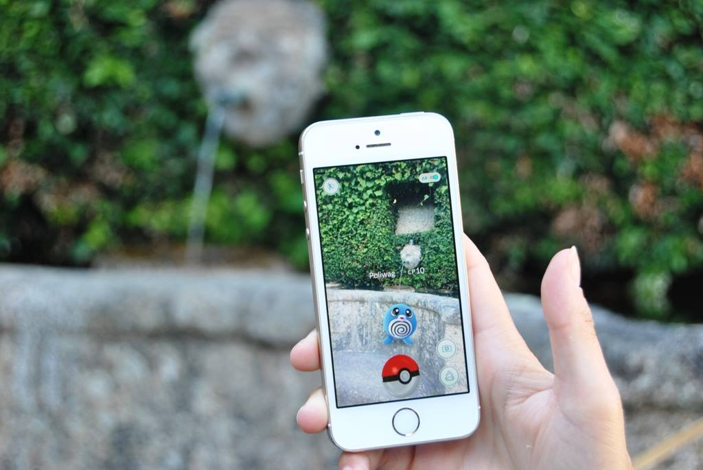 a phone shows pokemon near the fountain at casa do outeiro tuias
