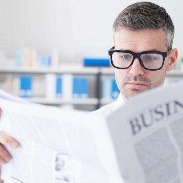 Hombre de negocios con gafas leyendo el periodico