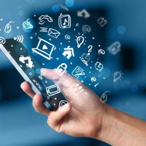 Hand hält Smartphone, auf dem Symbole der sozialen Medien zu sehen sind