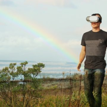 man walks through field with rainbow behind him exploring new tech trends like virtual reality