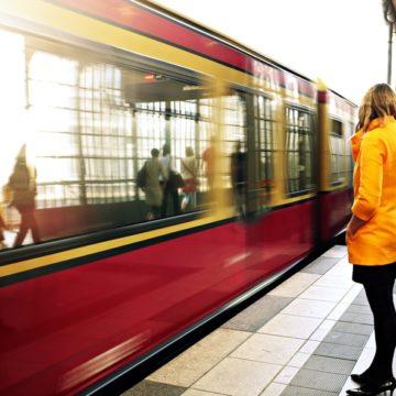 Viajera con abrigo amarillo a punto de tomar el tren