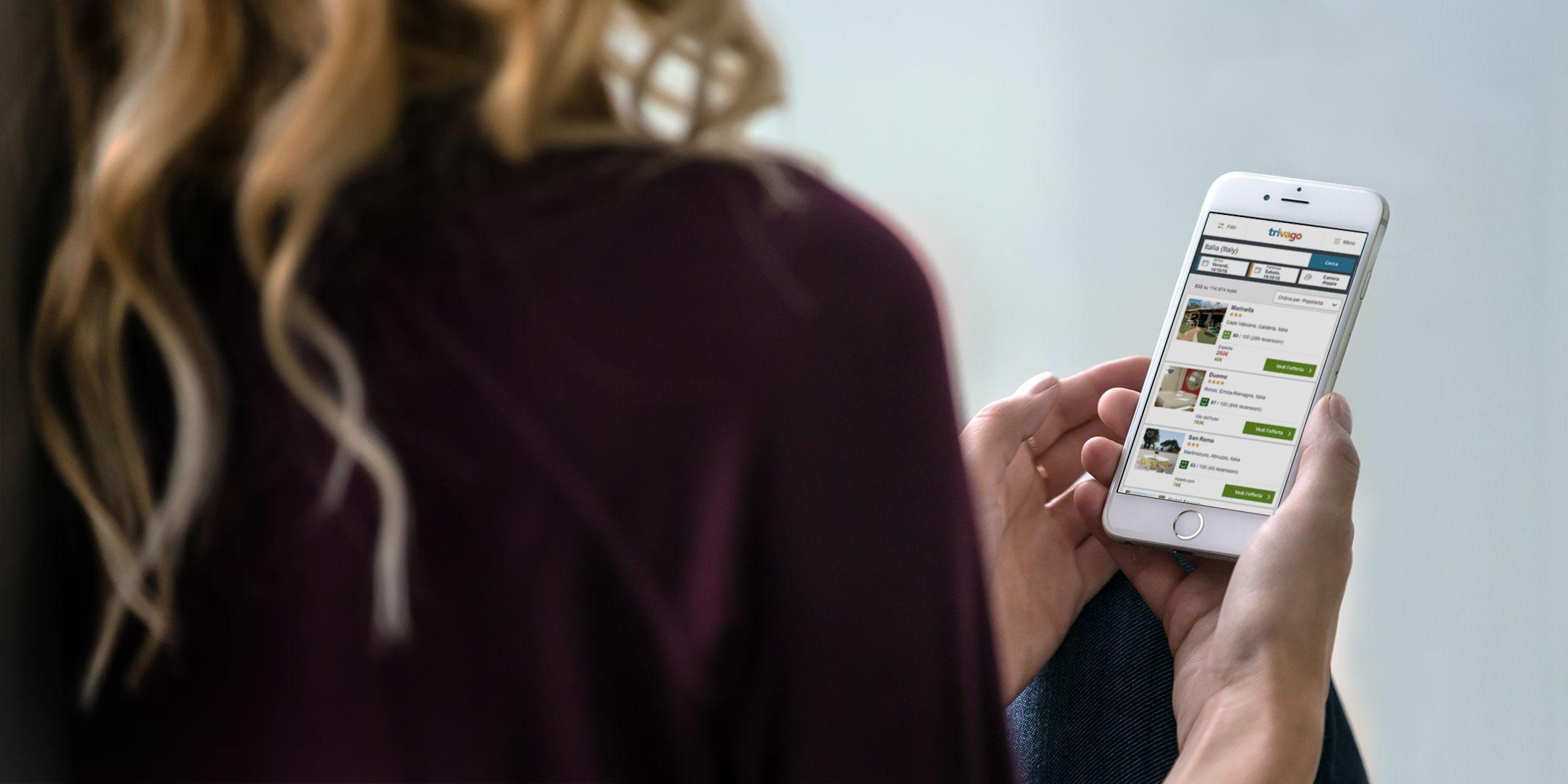 Donna che cerca un hotel su trivago dal suo smartphone