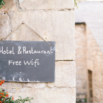 a chalkboard sign hangs outside of a hotel with a stone facade