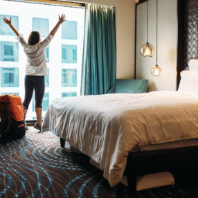 A woman stands at the window of a hotel room