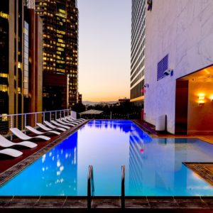 A modern American hotel exterior and its pool at dusk
