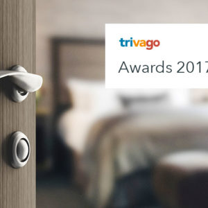 Quarto de hotel com porta entreaberta e logotipo do trivago Awards