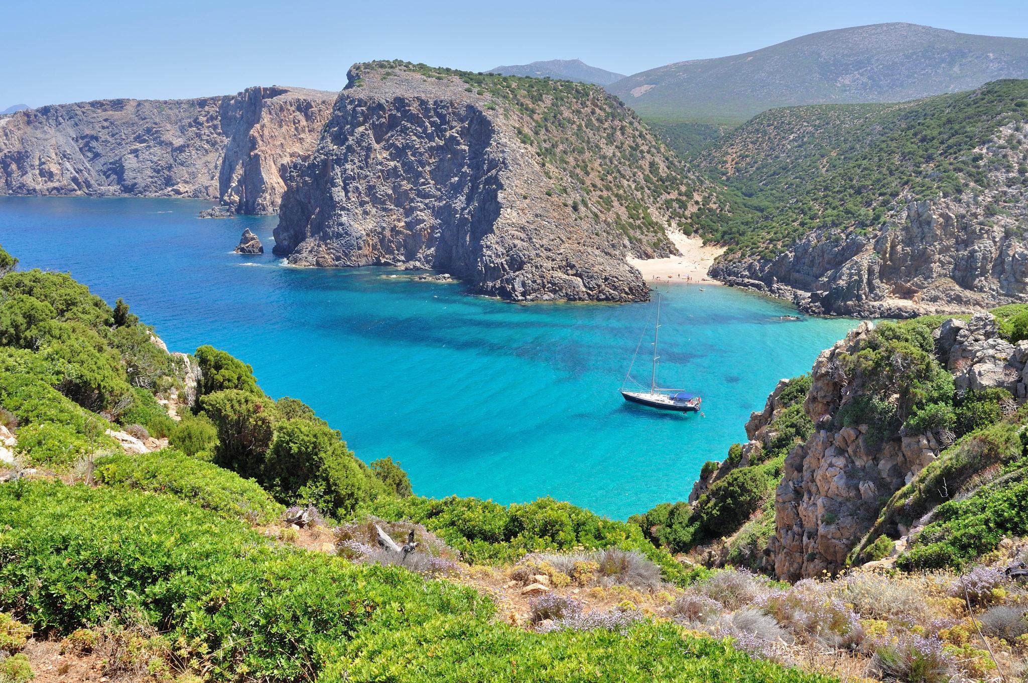 Barca a vela ancorata in una baia in Sardegna