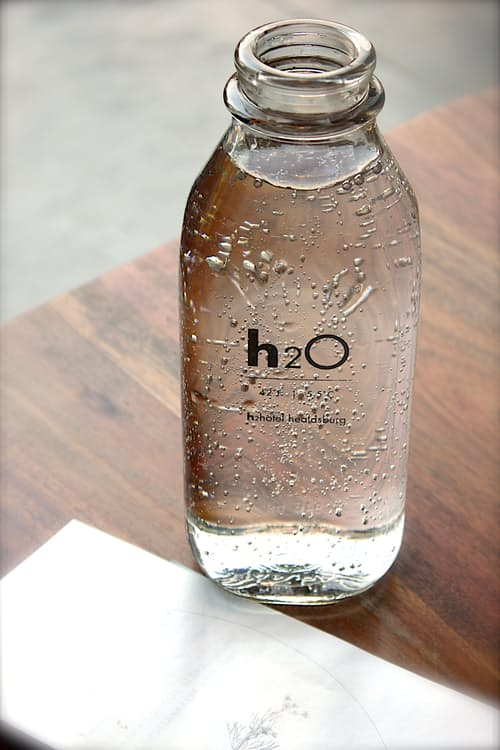 a hotels branded water sits on a desk with a note