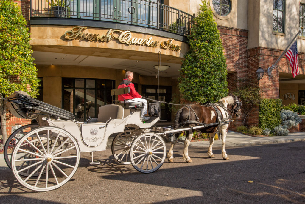 An exterior view of the French Quarter Inn with horse-drawn carriage
