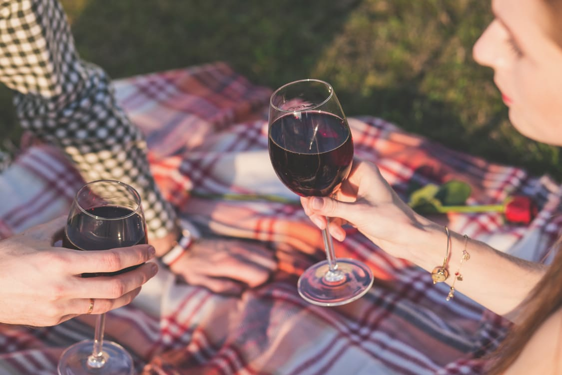 a couple shares wine during a picnic