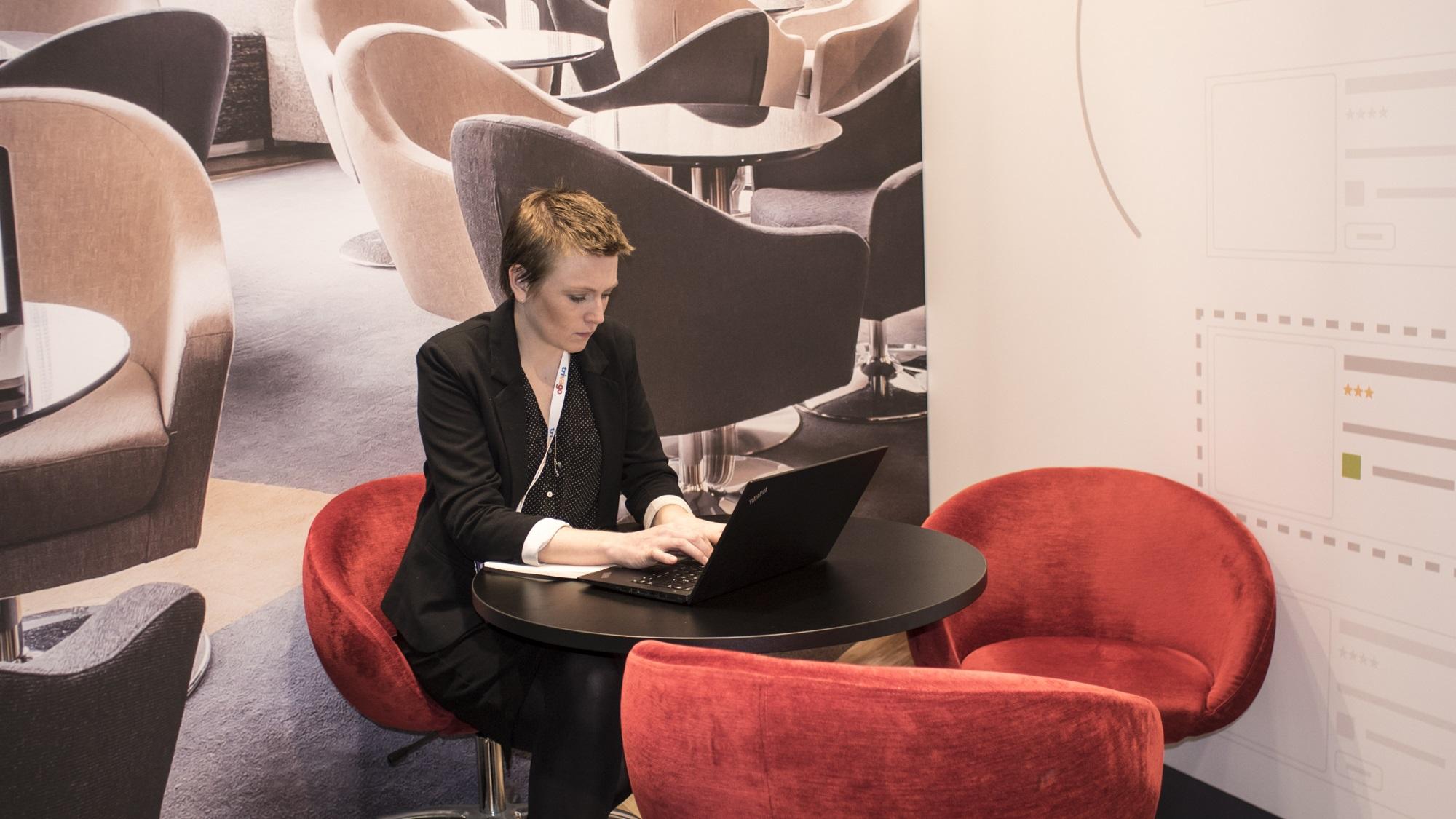 Eine Metasuchen-Marketing-Expertin auf dem World Travel Market arbeitet an ihrem Laptop