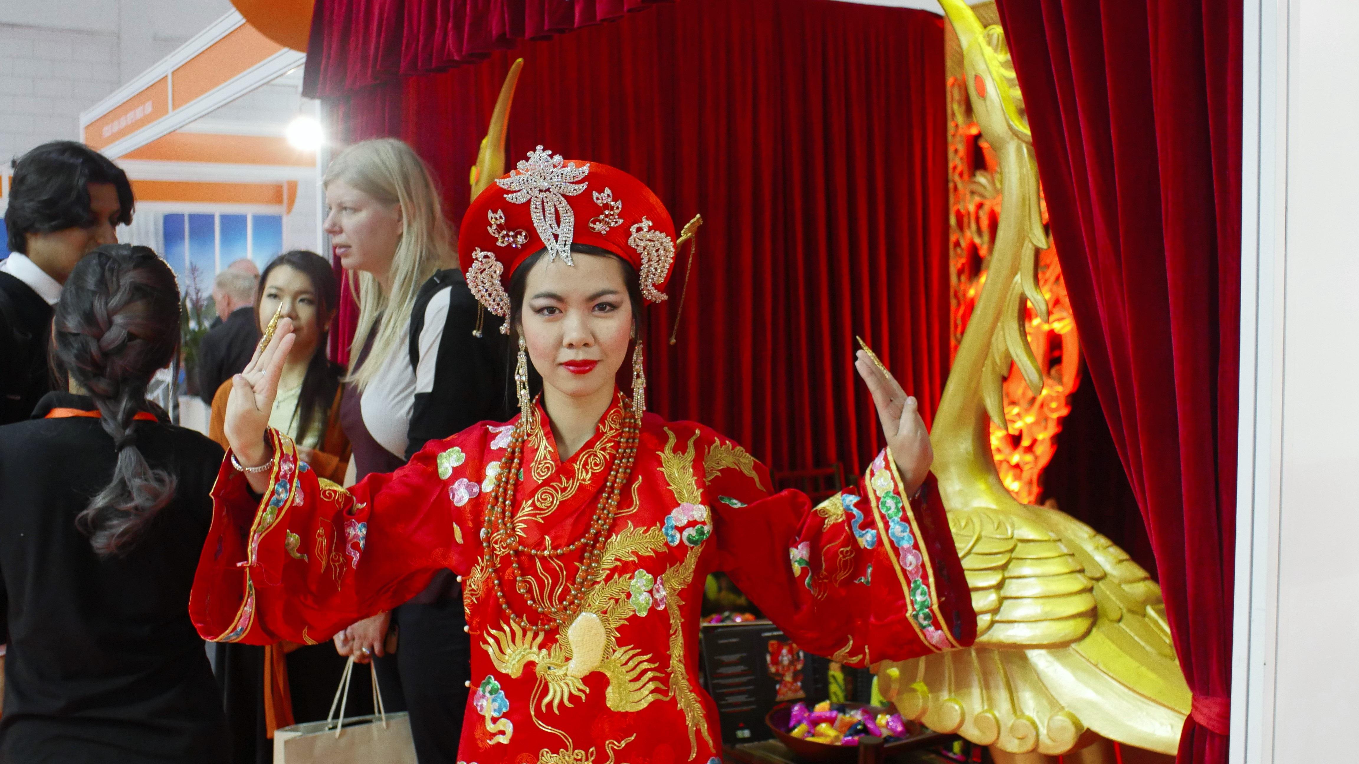 Frauen in traditionellen roten asiatischen Kleidern auf der WTM
