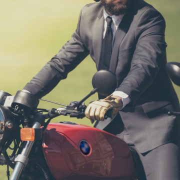 business traveler in a suit rides a motor bike