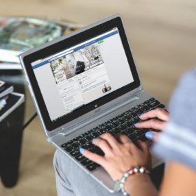 Mulher acessa o Facebook a partir do notebook em seu colo