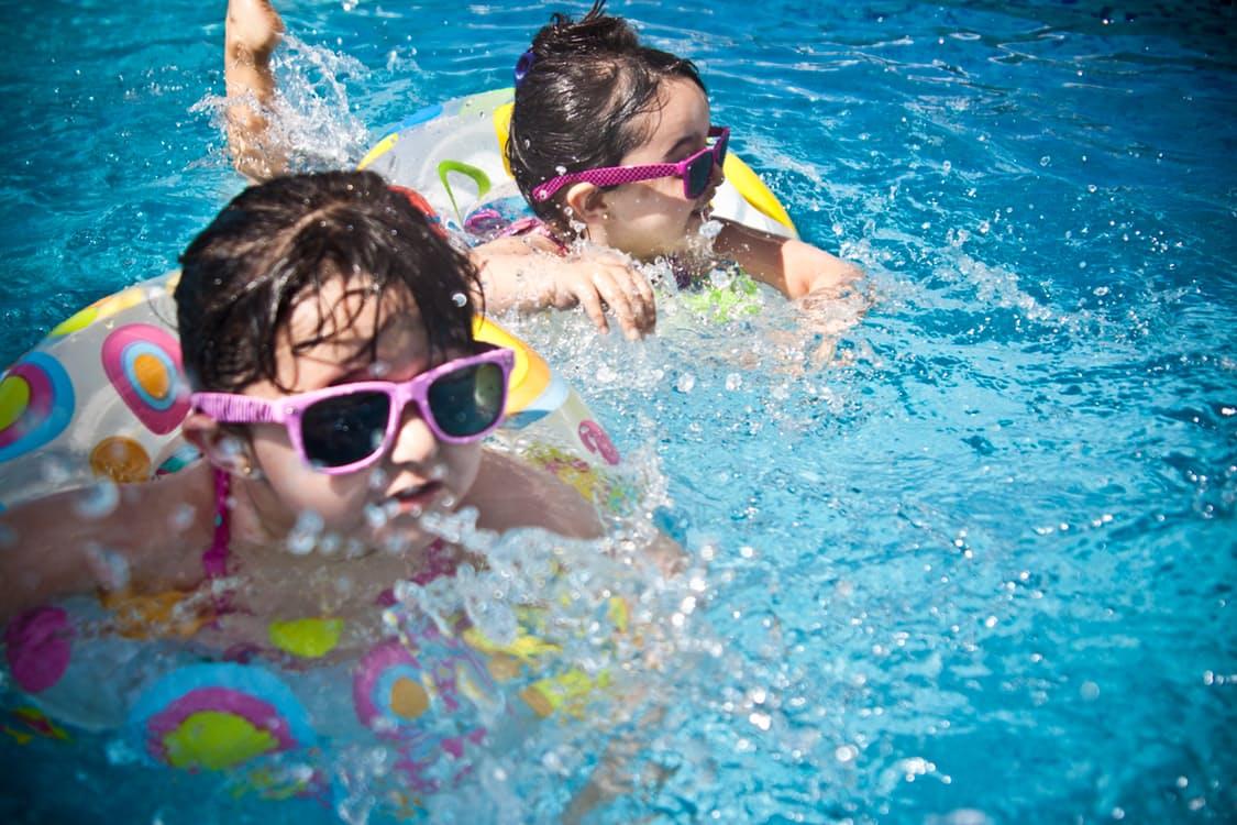 Due bambine con occhiali da sole rosa nuotano in piscina