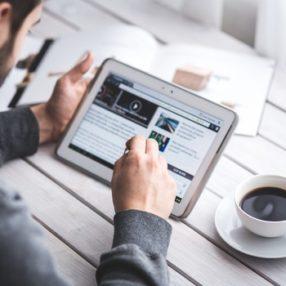 Uomo legge le notizie sul tablet e beve il caffè