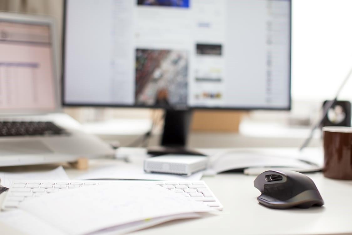 ένα ακατάστατο γραφείο με έναν υπολογιστή στο παρασκήνιο