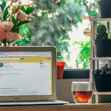 A laptop on a kitchen counter next to a cup of tea is set up for email marketing
