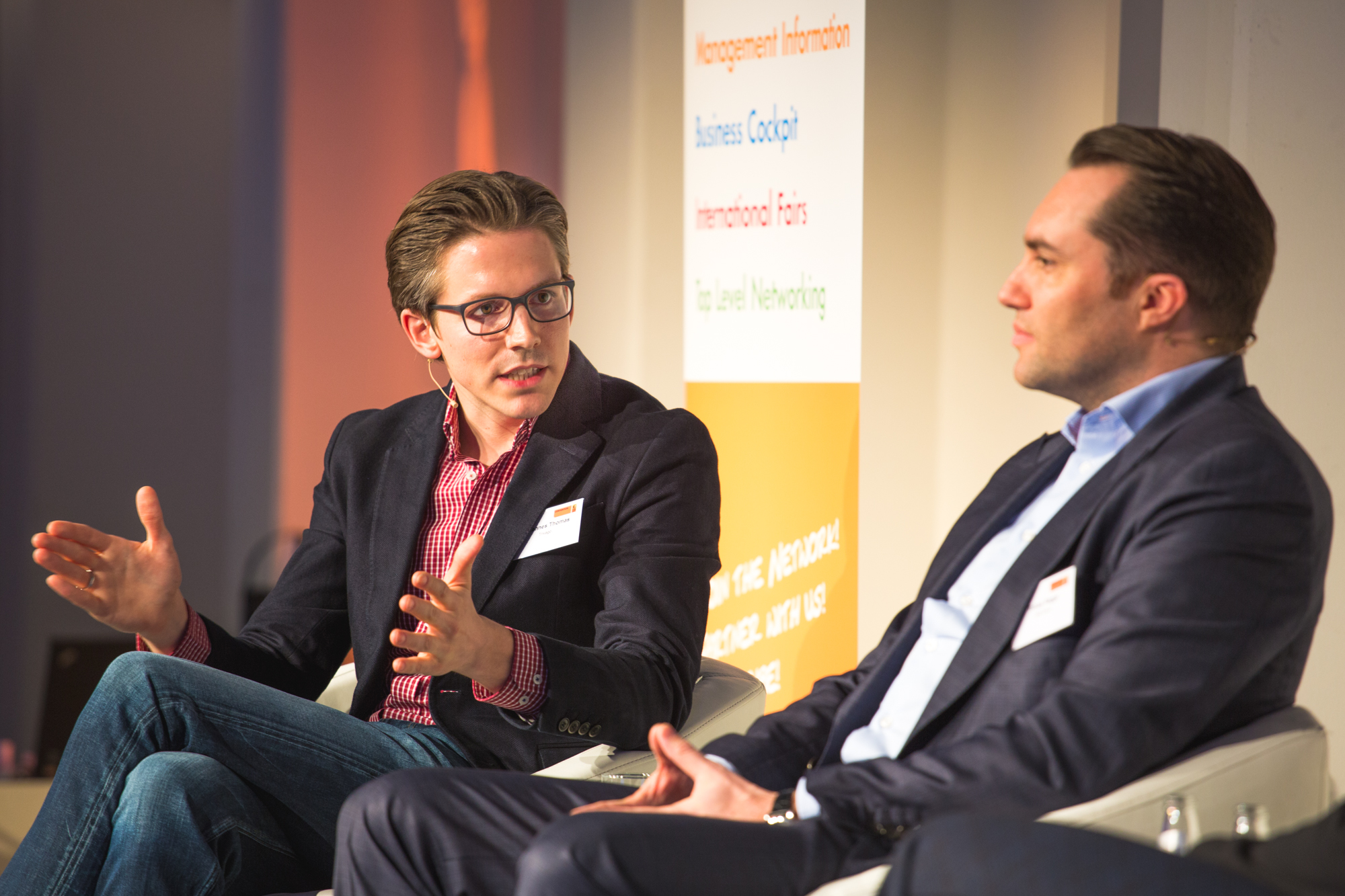 Johannes Thomas sits next to Tobias Ragge while speaking to the benefits of metasearch at ITB Berlin