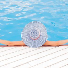 Una ragazza con cappello si rilassa in piscina