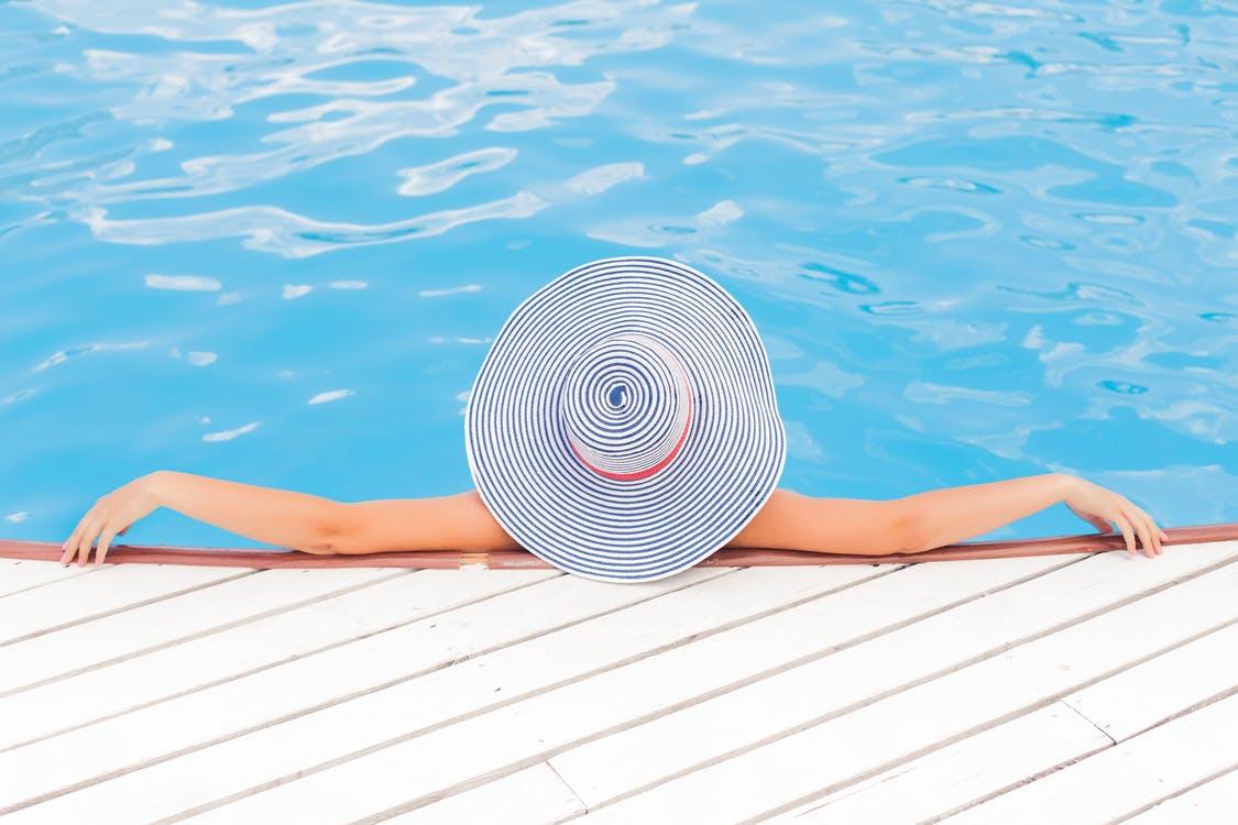 Blick von oben auf eine Frau mit großem Sonnenhut am Rand eines Pools