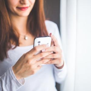 Eine Frau nutzt ihr Handy, um eine Frage zu stellen und sofort eine Antwort zu erhalten