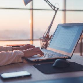 Un albergatore lavora al computer sui contenuti del suo hotel