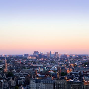 a skyline of Amsterdam at dusk, the location of the fourth annual Phocuswright Europe