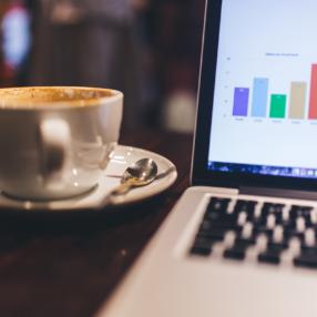 ένα ανοιχτό λάπτοπ που δείχνει τα αποτελέσματα από τις online καμπάνιες μάρκετινγκ, δίπλα σε ένα φλυτζάνι καφέ