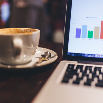 an open laptop showing the results of online marketing campaigns, next to a cup of coffee
