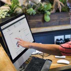 Una mujer sentada en una oficina mira a su ordenador y comprueba el rendimiento de su campaña de Rate Connect