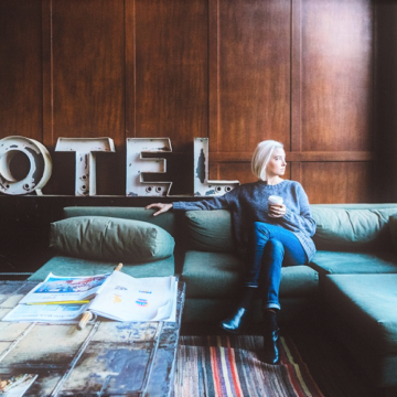A hotel guest drinks coffee while sitting on a couch in a hotel lobby