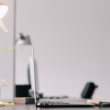 A hotelier's laptop is open on a desk with a modern lamp and a green plant