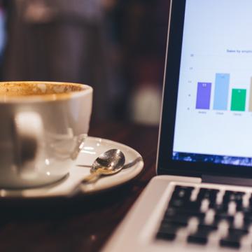 Eine Tasse Kaffee neben einem offenen Laptop, auf dem Ergebnisse von Online-Marketingkampagnen zu sehen sind.
