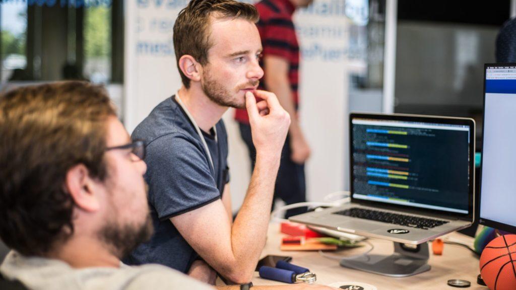 Dos hombres trabajando delante del ordenador