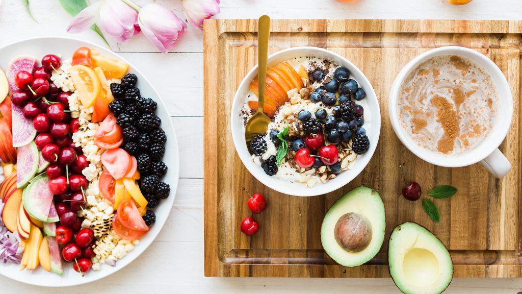 Un piatto pieno di frutti tropicali, un avocado e una ciotola di fiocchi d'avena