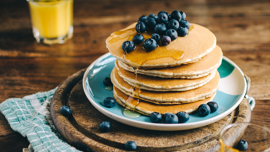 A plate of pancakes with blueberries and a glass of orange juice in the background
